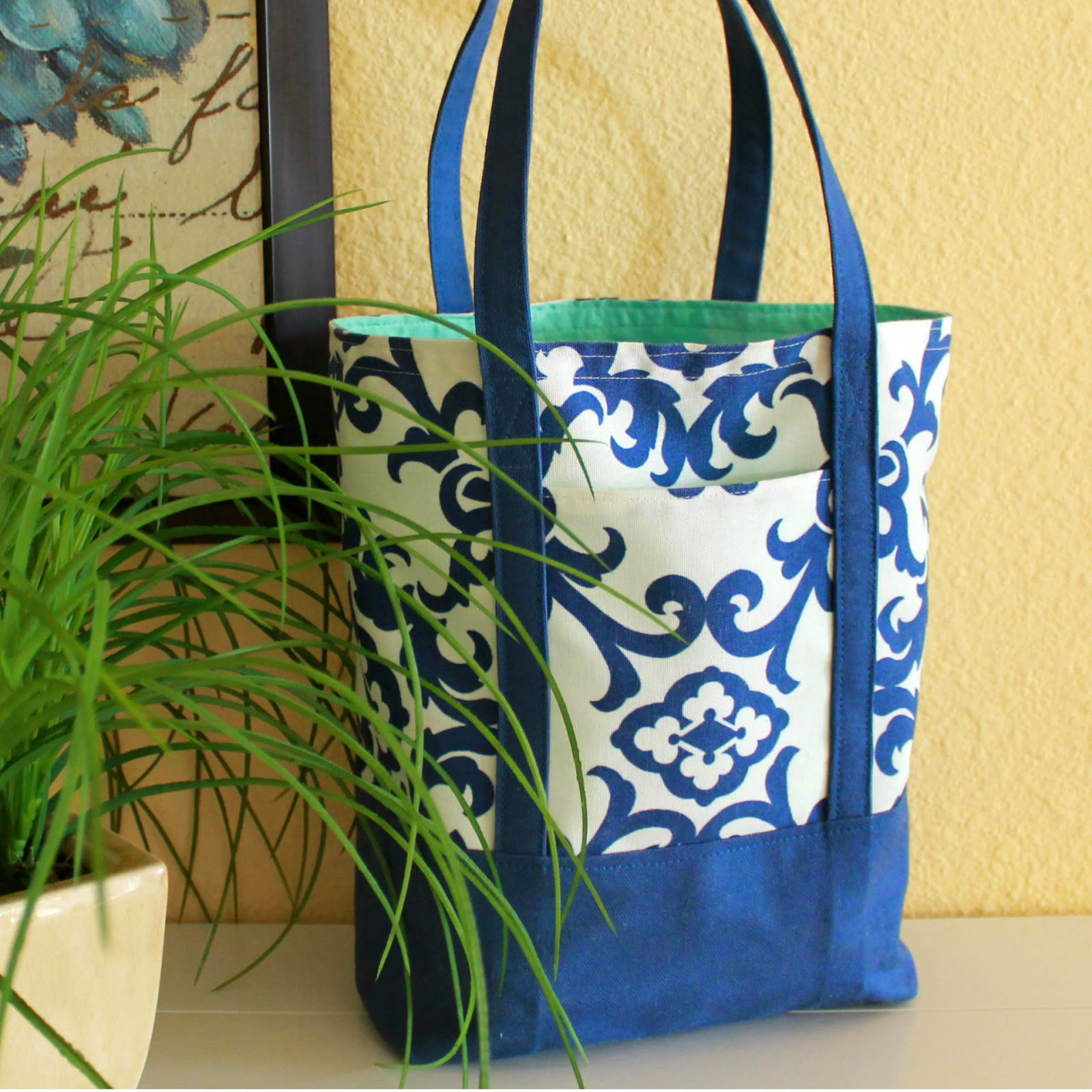 A blue and white canvas tote by a plant