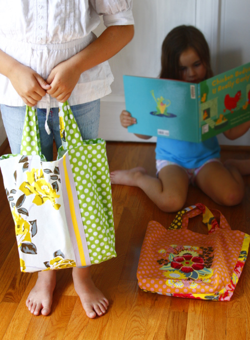Two children with totes made from dish towels