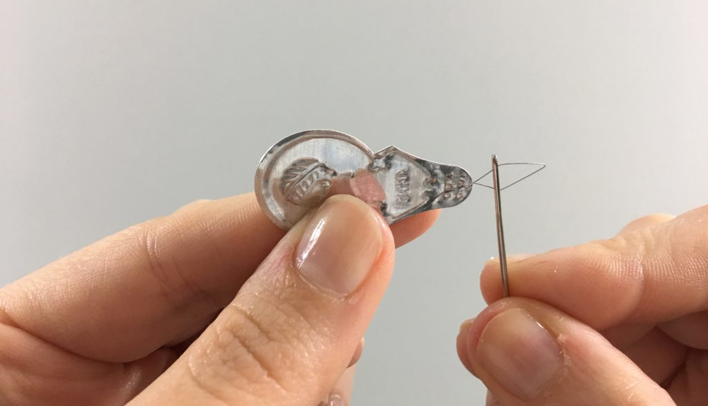 Inserting a needle threader into the eye of a needle