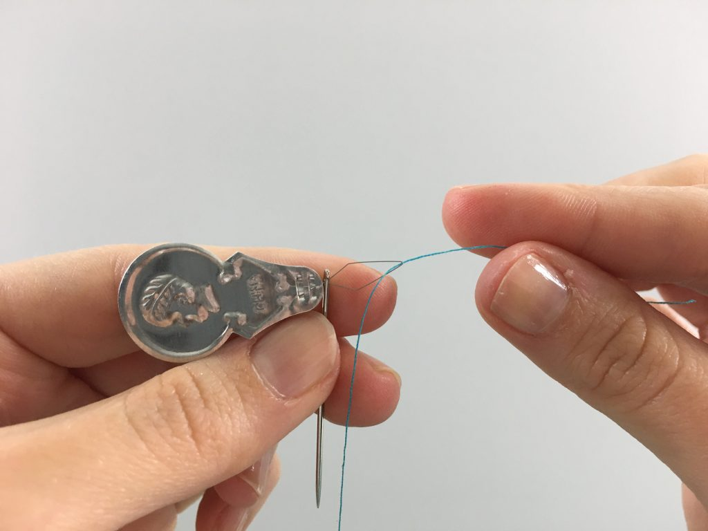 Pulling thread through a needle threader