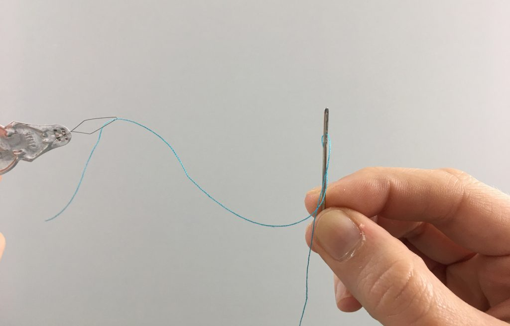Finishing threading a needle with a needle threader