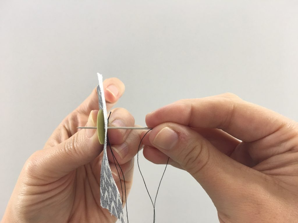 Inserting a needle into a button hole
