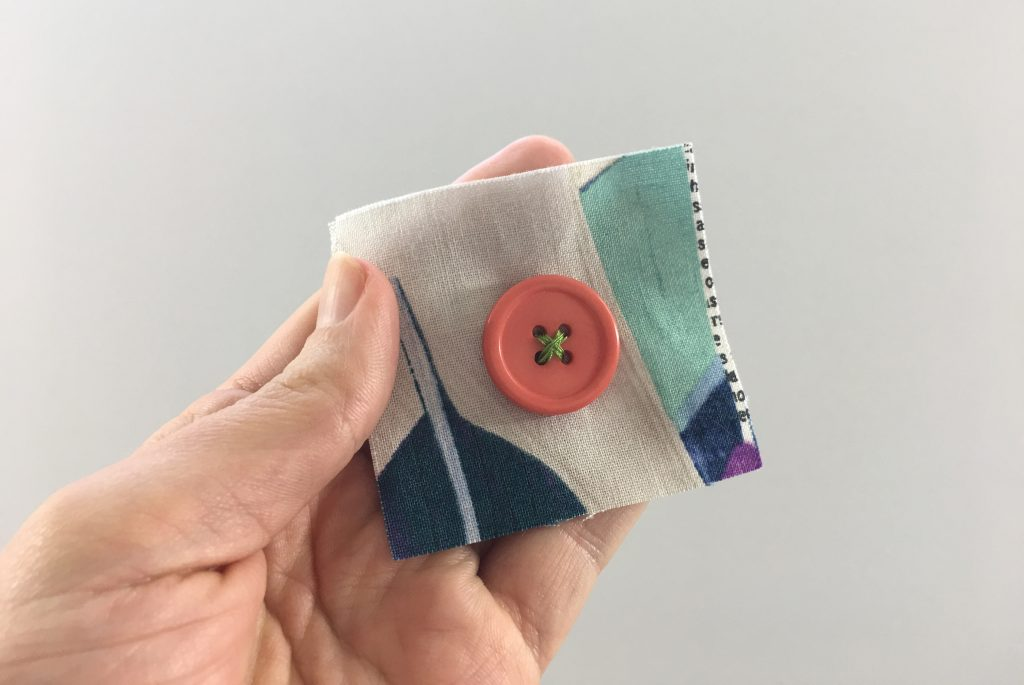 A sewed on four hole flat button