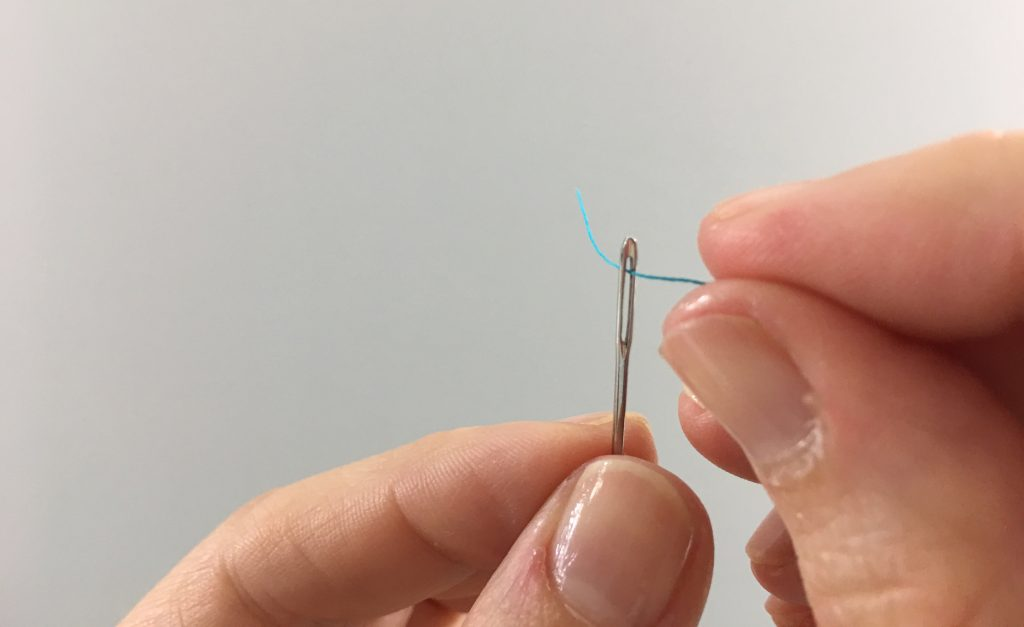 A thread being inserted into an eye of a needle