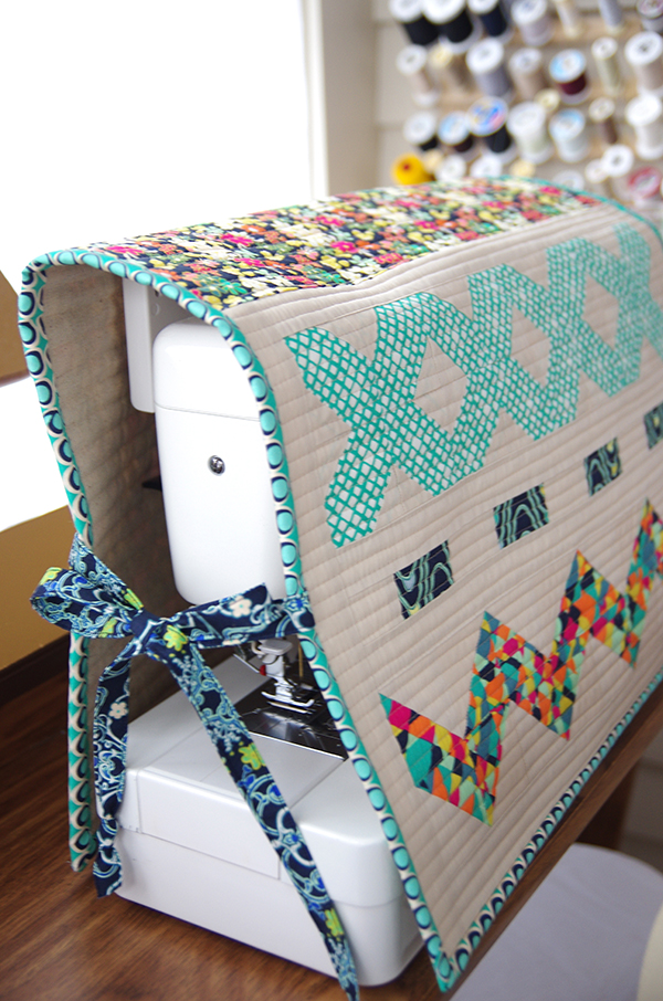A quilted sewing machine cover with applique