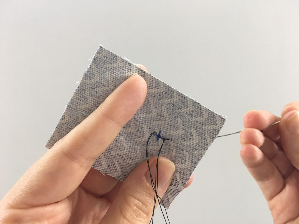 Pulling needle through fabric