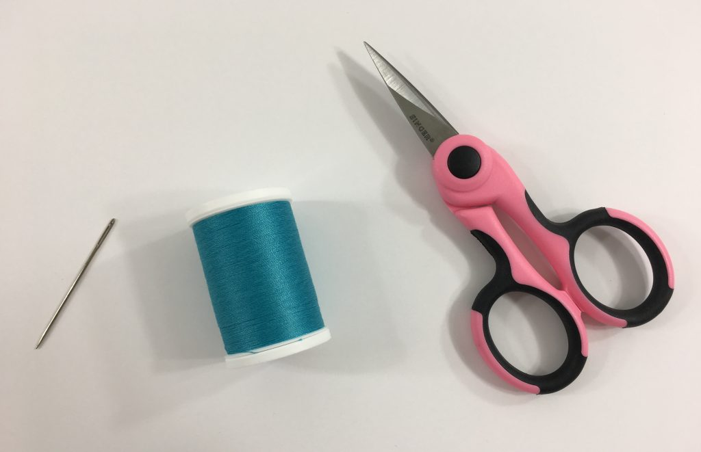 A sewing needle, spool of thread, and scissors