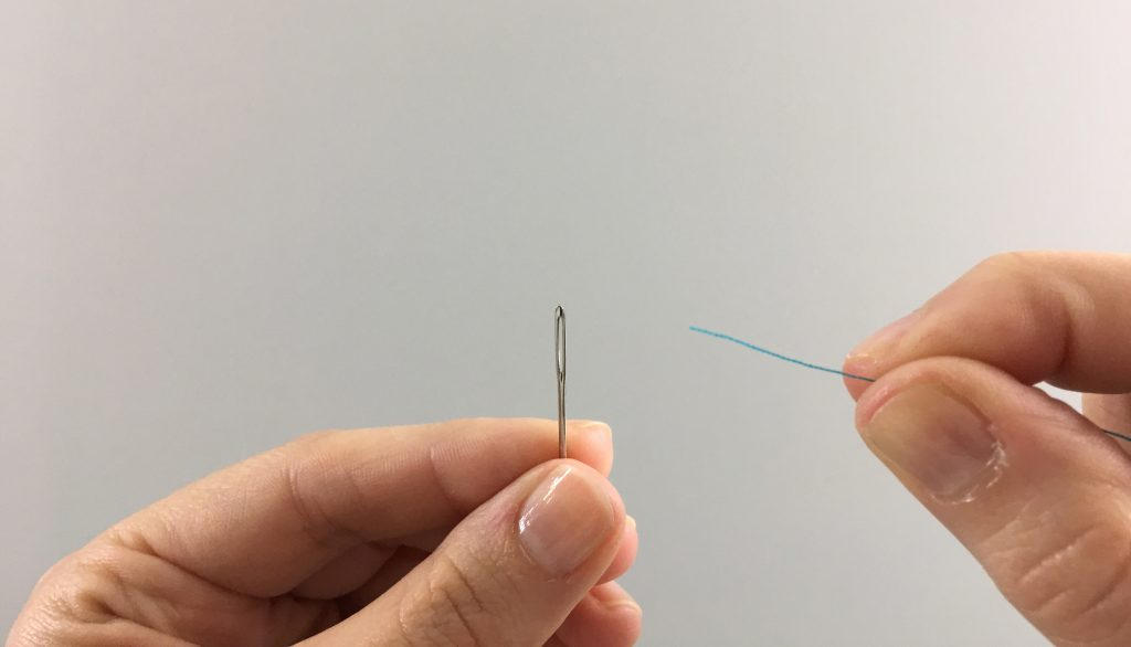 Thread pointing at a needle