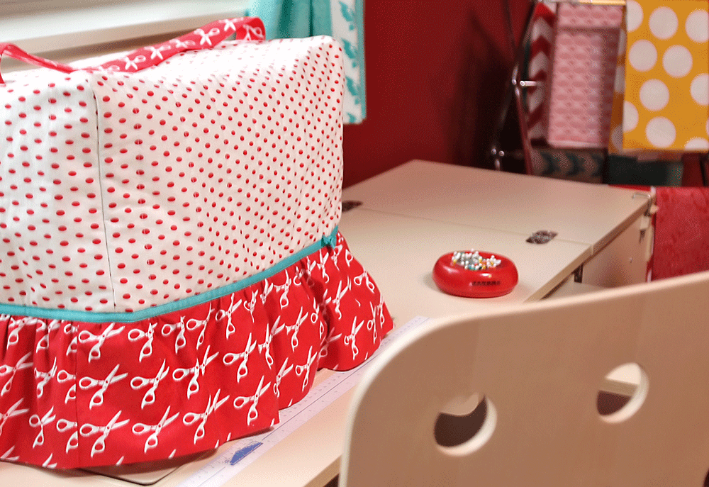 A red and white skirted sewing machine cover