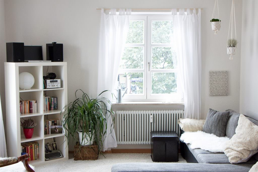 A living room with two macrame plant holders in the corner