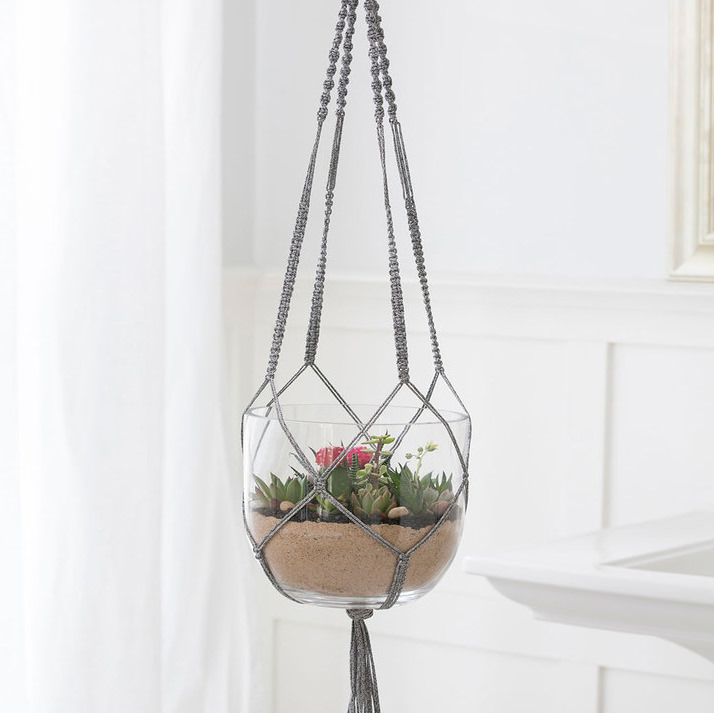 A macrame plant hanger made out of gray yarn