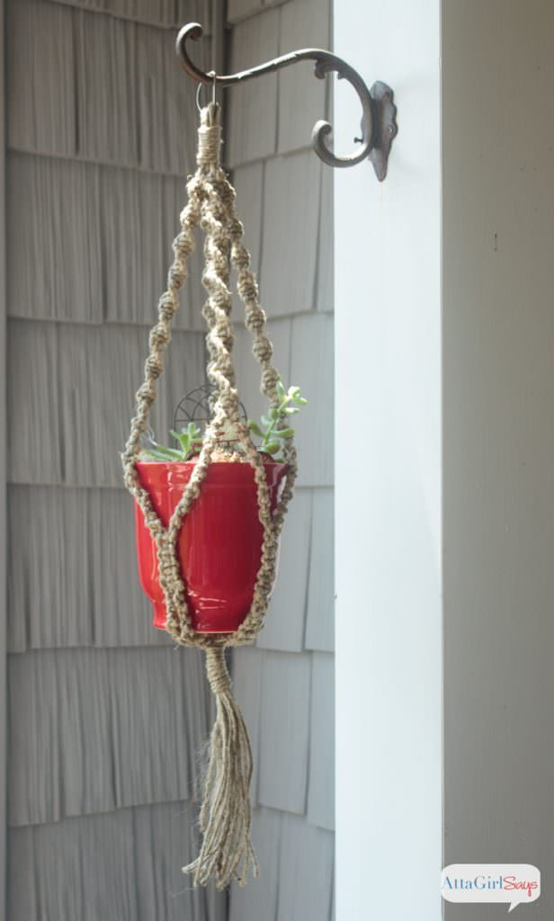 A red pot in a macrame plant hanger